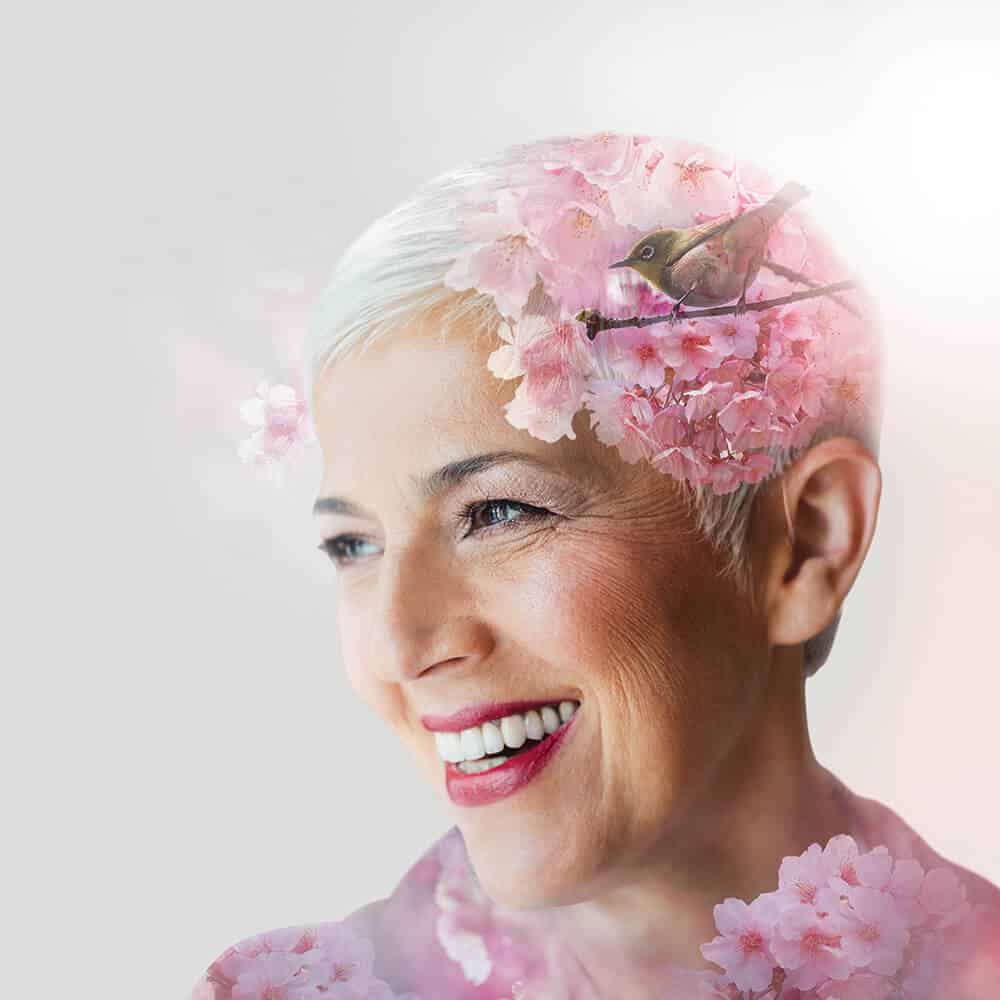 Elderly woman with flowers and birds in hair